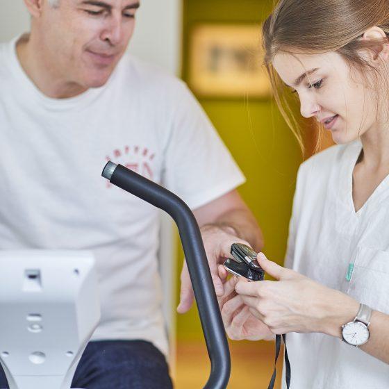 mise du capteur cardiaque au doigt du patient ce trouvant sur un vélo d'appartement